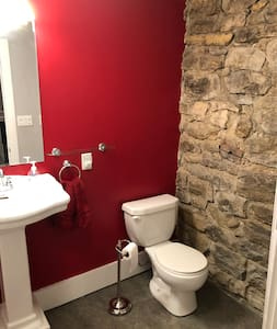 This shows the toilet. The bath is oversized, with standard tub/shower and pedestal sink. There is a small step up into the bath from the master bedroom.