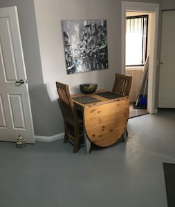 The bathroom door is to the right of the dining table. It is a sliding door and there is a tiny step up