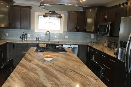 Kitchen has access all around the island and is open concept with the main floor. There are 2 steps in the front entry from the driveway, but not together and entrance is 36 inches.