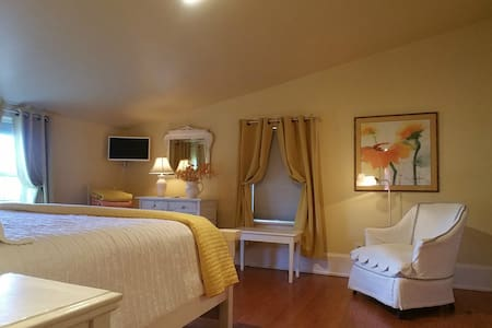 There are pine floors and ample space on either side of the king bed.