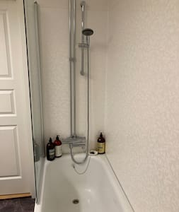 Vi har ett badkar med handhållen dusch.   We have a bathtub with a handheld shower.
