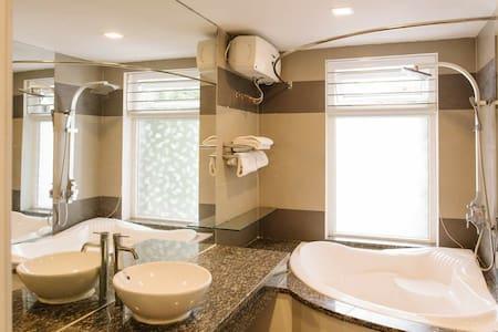 Spacious, stylish bathroom with bathtub and shower rain.