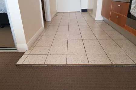 There is a 2cm height difference between the carpeted area and tiled entrance.