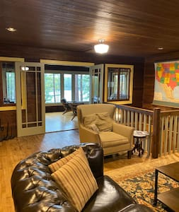 The double doors lead to the dining room which has seating for 12 along with an adjacent sitting area and access to the outdoors via a side door and 2 exterior steps.