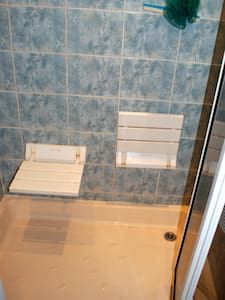 Two seats fixed to wall in shower area