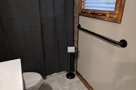 Secure, bolted, grab bar directly in front of toilet which doubles as an extremely strong towel bar.