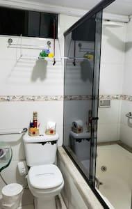 Barras de apoio ao lado do vaso e dentro da banheira, no entanto o chuveiro localiza-se dentro da banheira existindo um degrau para acessá-lo.