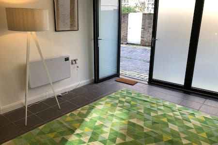 The downstairs bedroom has its own entrance pictured here. These are bifold doors which can be further opened up to allow for accessibility. The room is practically flush with the street.