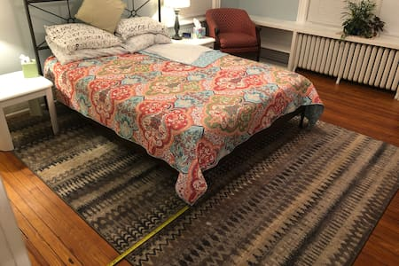 Queen bed with minimum 44 inches at bottom of bed and on both sides.