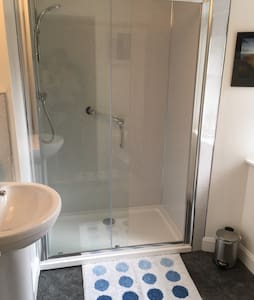 Walk in shower with hand rail.