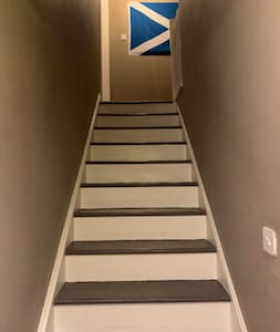 A flight of stairs from the hallway to the bathroom and bedroom area of the property