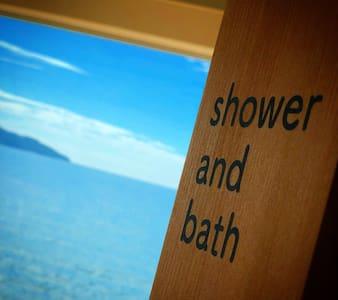 レインシャワー設置のシャワールームとその奥に海の見える露天風呂がございます。