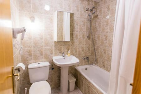 In the bathroom, you will find a sink and bidet, both with warm water. Enjoy the bathtub with a handheld showerhead + mount and shower curtain. You will also find toilet + paper + brush, a hairdryer,  bathroom cup, a dust bin, and a mirror cabinet.
