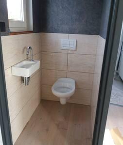 opklapbare beugel op linkerzijde van toilet en zithoogte aangepast.