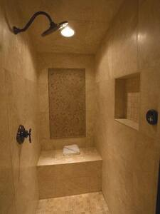 Master shower has seating area