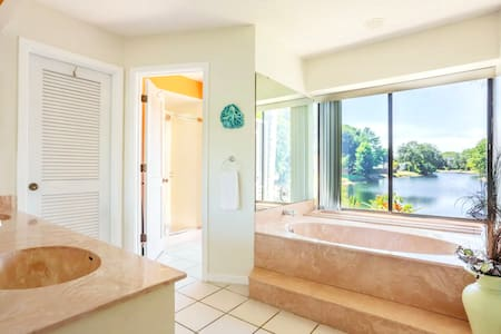 A very wide doorless entry from the bedroom to the bathroom. where the sinks and jacuzzi are located. From there is a door to the toilet/shower room.