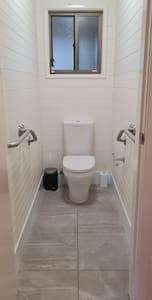Grab rails on both sides of toilet from door to toilet. Toilet is slightly higher than standard to accommodate mobility impaired. Grab rails are bolted to walls.