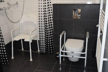 Ruime rolstoel toegankelijke badkamer. Muursteunen aanwezig bij douche.  Wastafel laag.