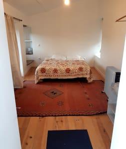 cette chambre est côté terrasse.  Il faut pas monter l'escalier pour y accéder mais pour aller à la salle de bain/toilette il faut traverser une partie de la terrasse qui sépare cette piece de la maison.