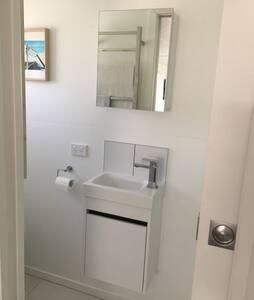 En-suite bathroom - toilet, shower 900x900mm, hand basin vanity and heated towel rail.