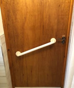 A wide entrance to the bathroom with a grab rail on the inside of the door.
