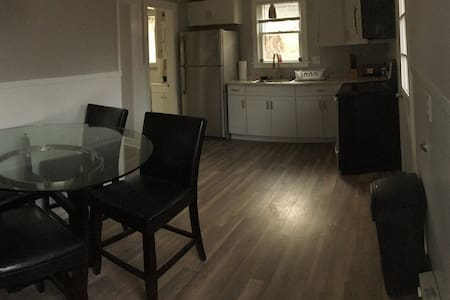 The bedroom is between the dining table set and the bathroom/refrigerator area.