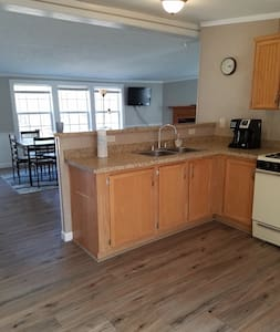 Full kitchen with set of utensils. Gas stove, a refrigerator and sink.