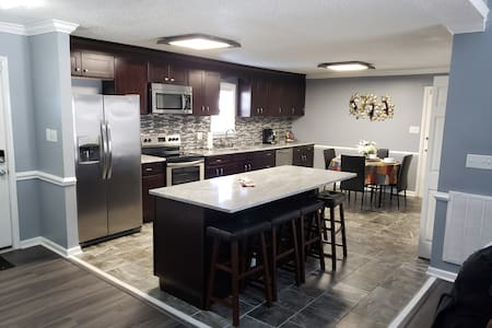 Very spacious kitchen with island and bar stools also a glass kitchen table with 4 chairs.