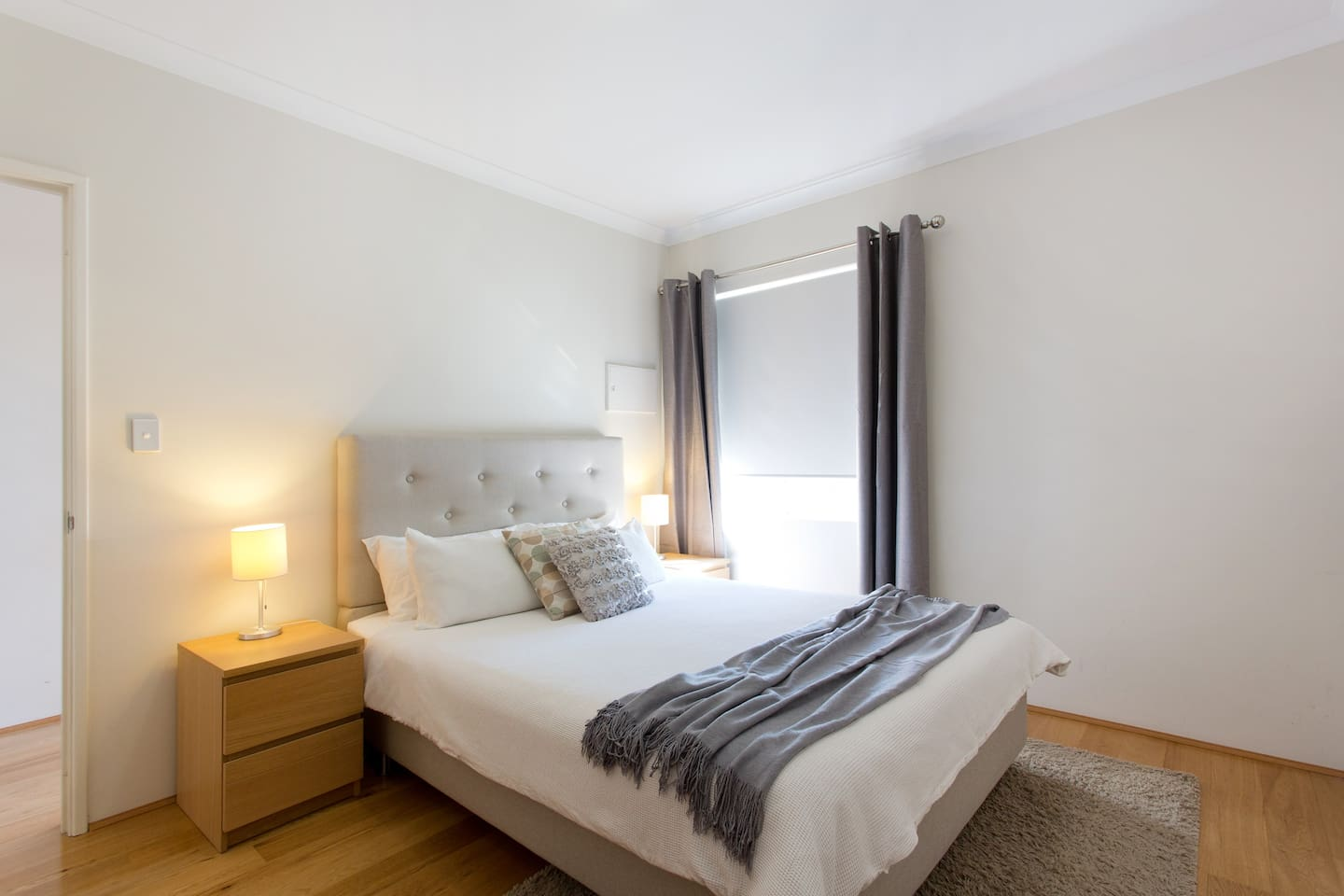 Peaceful bedroom with neutral decor and block out curtains on top of roller blind. Plenty of pillows and linens supplied.