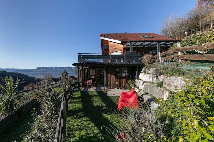 Vous pourrez apprécier la vue panoramique sur la nature et les montagne depuis votre terrasse privative attenante au gîte située au rez de chaussée de notre chalet.