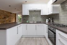 Full kitchen with fridge, freezer, microwave, dishwasher and washing machine