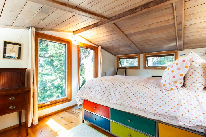 Six large windows + skylight keep this loft bedroom lit up with excellent light + cross-ventilation open to the forest.