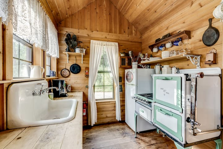 The kitchen is fitted with an antique gas stove from the 1920s, the cooktop still works perfectly for whipping up eggs and pancakes! Other salvaged and vintage accents create a charming place to make a meal.