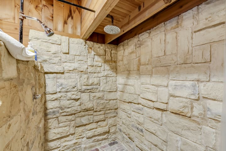 The bathroom features a large custom shower with rain shower head, brick floors, and stone walls.