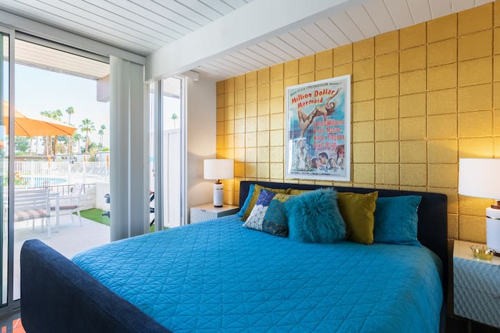 """Highly upgraded West Elm furnished bedroom.  King size bed, with a pool blue coverlet.   Ample light with gold metallic wall highlighting """"Million Dollar Mermaid"""" Esther Williams poster.  Puts you in the mood to do some pool laps.....or not!  Love."""