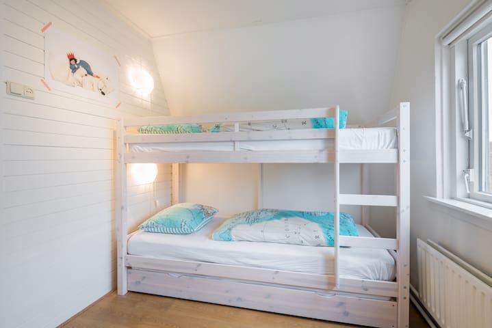Bovenverdieping: slaapkamer met stapelbed, en nog 1 extra matras in de uitschuiflade.