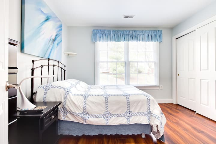 A small, blue bedroom with a TV.