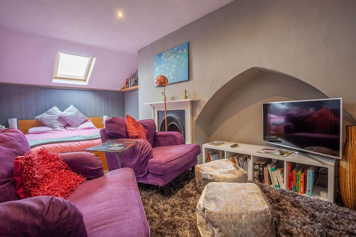 Wide curl-up in chairs and footstalls. A large Sony smart TV plus a large selection of reading material.