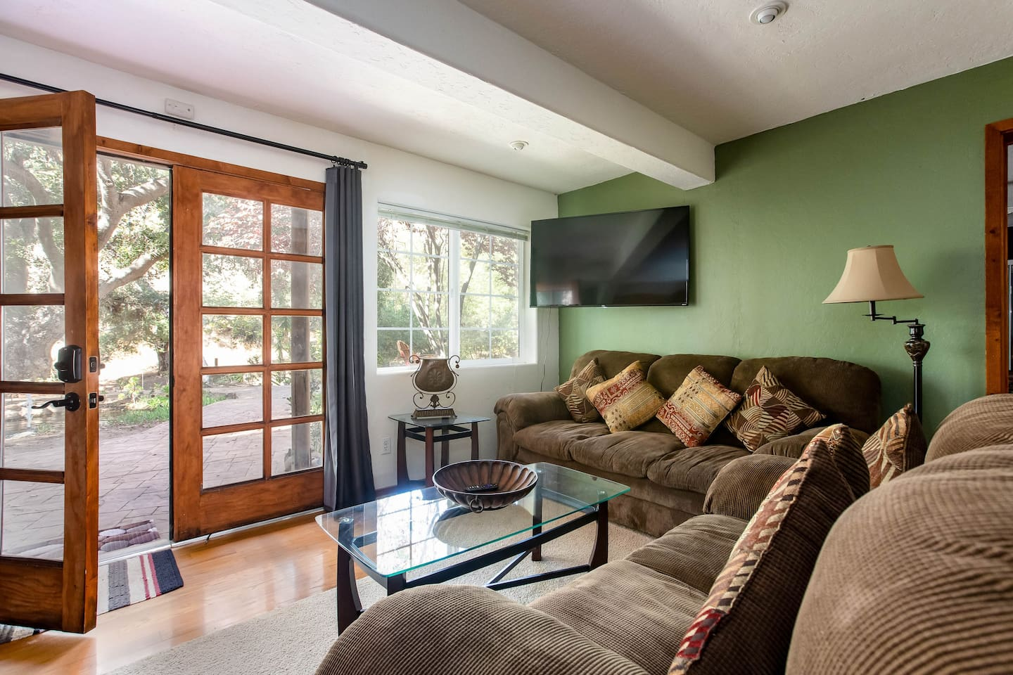 Welcome to Dragonfly Suite. Drenched in natural light and overlooking the spectacular view of the oak tree canopy, waterfall, fountain and stream in this private backyard. (Notice the smart TV and french doors)