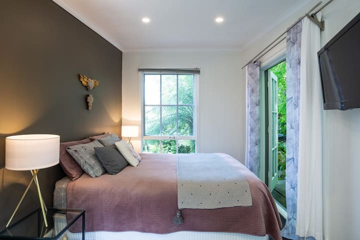 Wouldn't you like to wake up in this light filled bedroom with views of the lush fern filled rain-forest garden