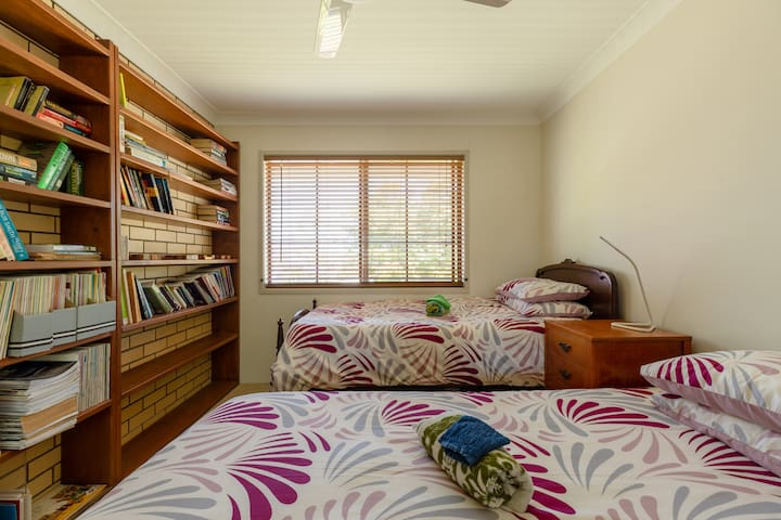 Library & 3rd bedroom features two king single beds, ceiling fan and plenty of reading material.