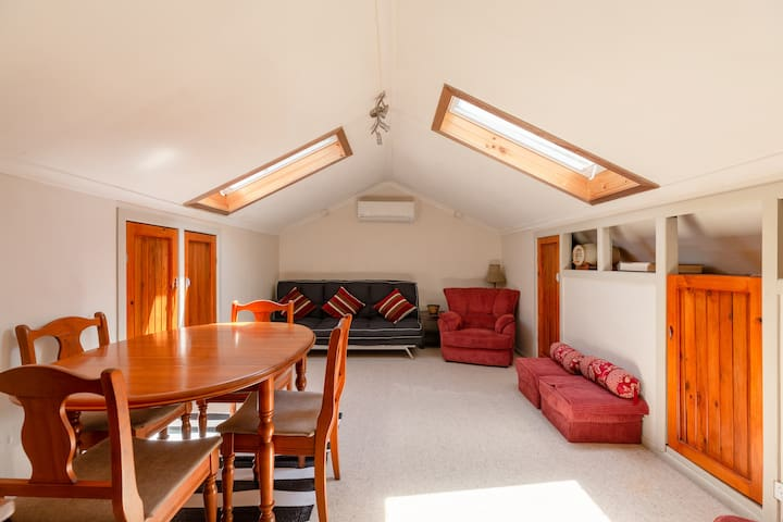 Funky attic/lounge with sofa bed and stretcher bed in cupboard.