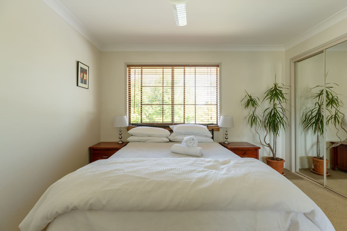 Main bedroom features a queen bed, ceiling fan, laptop study desk and large wardrobes.