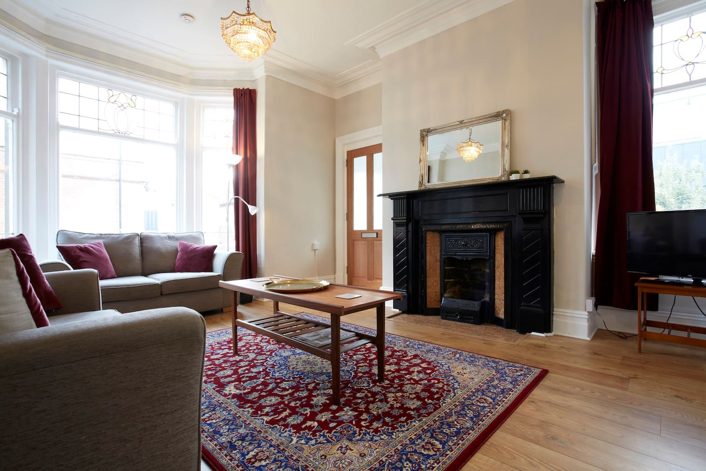 Lovely bright Victorian sitting room. The bay window and window to the side have the original stained glass panels. The  feature fireplace make it feel really cosy in the evenings.