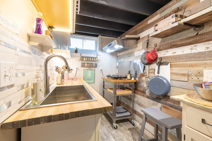 Pots and pans, caserol dishware, mixing bowl, storage bags, two door refrigerator with freezer.  Has two benches for sitting at the counter table; exhaust fan, coffee mugs, creamers, coffee assortment; wine and margarita glasses, dishes, can opener.