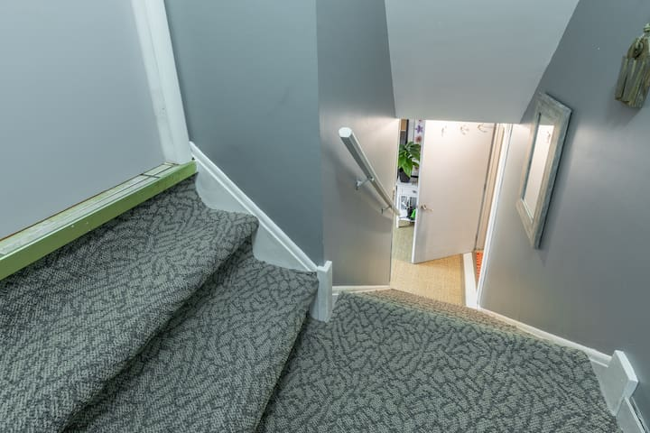Steps coming in from garage; suite is down the steps, door on the right side; console table with umbrellas, first aid kit;