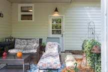 guests and their pets are free to relax on the porch; smoking allowed in this area; shown is the entrance door to the garage; once inside the garage, the door on left goes down to the suite;  one acre to enjoy in back w/firepit.  Lighted at night.