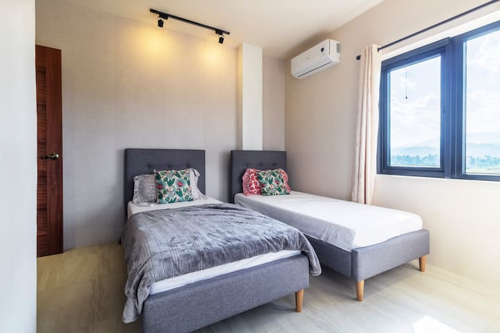 2nd floor Twin bed room with mountain views. A dresser with mirror, aircon, and blackout curtains provided in all guest bedrooms