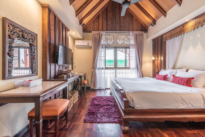 The second bedroom decorates with a princely high gable roof in classical Lanna style with a teakwood grand king bed, two multipurpose tables with wood carving mirrors, with Air Conditioning and Cable TV.