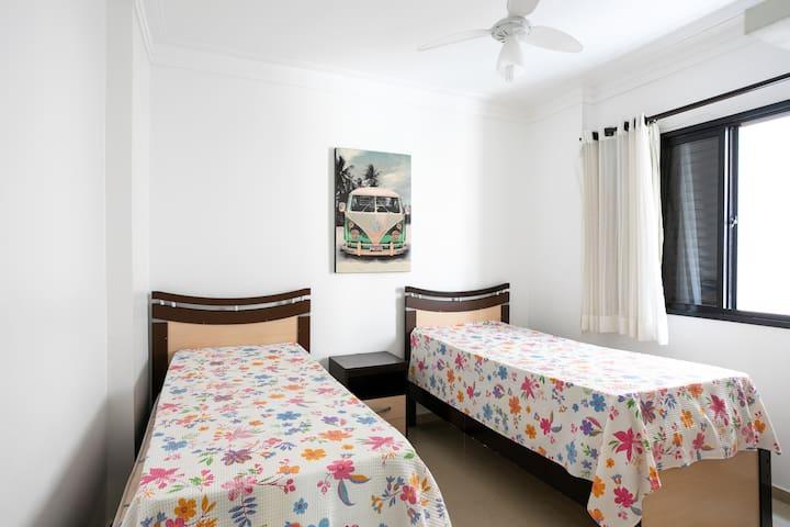 esse quarto tem uma cama de casal e uma de solteiro e ventilador no teto.